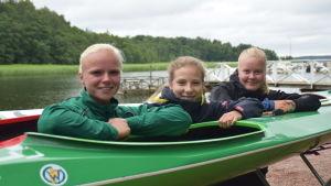 Emma Malmsten, Elvira Johansson och Jenni Sandberg lutar mot en kanot.