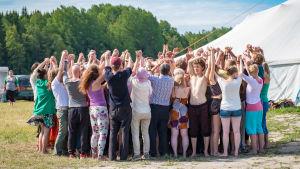 Ihmisiä seisomassa piirissä kädet ylhäällä, taustalla valkoinen teltta