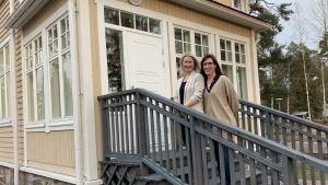 Emelie Hindsberg-Lipponen och Maj Estlander står utomhus på trapporna till Villa Solhaga i Grankulla. Vinden blåser i deras hår då de står på den gråa trappan till det gula huset, de ser in i kameran och ler.