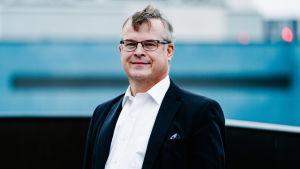 HUS diagnostikchef Lasse Lehtonen fotograferad utomhus. Han är klädd i kavaj och skjorta och tittar in i kameran och ler.