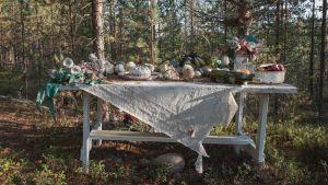 Asetelma pöydällä, pullo, muovikukkia, taideteos