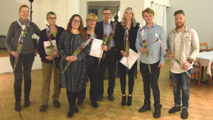 en grupp människor med rosor och diplom.