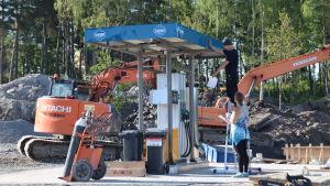 En ny bränslestation installeras på ett byggområde. Två personer står och inspekterar stationen. I bakgrunden syns en orange grävskopa.