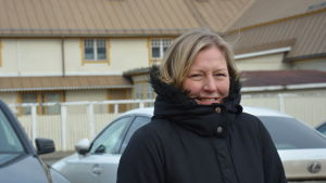 Sari står utomhus i en svart jacka. I bakgrunden FBK-huset i Pargas.