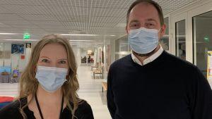 En kvinna och en man står i skolkorridor, bägge bär munskydd.
