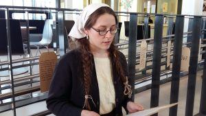 En flicka står framför ett staket och läser en text om hur fångar behandlades på Åbo fångläger 1918-23.