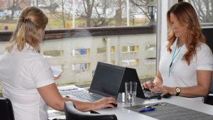 Sanna Pöyhölä och Paula Agge vid sina datorer. Kollar om det finns lediga sjukskötare som kunde hoppa in i sjukdomsfall.