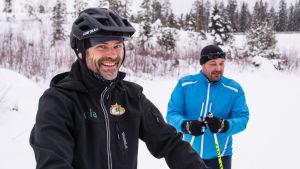 john björkskog med cykelhjälm och markus lindroos med skidor i skidspåret
