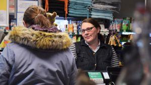 En kvinna sitter i en kassa i en liten livsmedelsbutik, i sällskap av en kund som har ryggen mot kameran.
