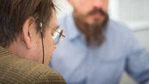 I förgrunden sitter en medlare med glasögon, i bakgrunden sitter Sami.