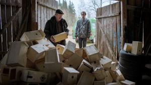 Nisse (Peik Stenberg) och Stefan (Martin Paul) står i dörren till ett lider som är fullt med fågelholkar..