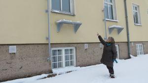 En kvinna står ute i snön och pekar upp mot ett fönster på ett stort gult hus.
