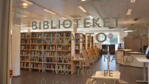 Texten Bibliotek Kirjasto på en glasdörr med många hyllor med böcker i bakgrunden.