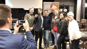 Flera glada personer står och poserar för ett fotografi. Heikki Vestman står i mitten och pekar mot fotografen som synns till vänster i bilden.
