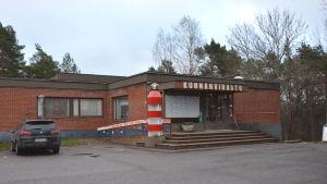 Gustavs kommunkansli, en låg, röd tegelbyggnad med platt tak.