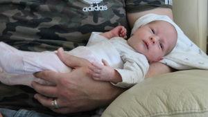Ett litet spädbarn som ligger i famnen på en man med grön kamoflagetröja.