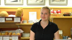 Sara Haglund står bakom kassan, i bakgrunden synns hyllor med bröd och assietter.
