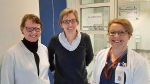 Tre damer, Jaana Koskenniemi, Laura Viikari och Tarja Eronen, står vid en öppen sjukhusdörr.