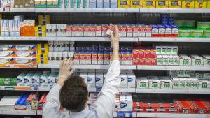 En apotekare fyller hyllorna med smärtstillande mediciner.