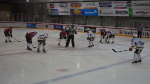 Tekning, domaren släpper ner pucken i matchen Malax IF-IFK Lepplax, division 3, december 2016.