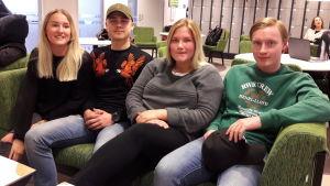 Fyra 18-åringar i soffan i skolans aula, glada, ser in i kameran.