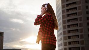 En kvinna står utomhus med ryggen mot kameran och lyssnar på något i sina hörlurar.
