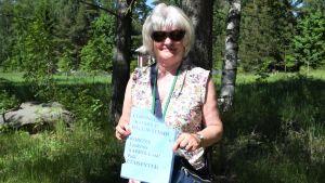 En kvinna med en lapp i handen.