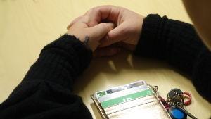 kvinnohänder på bordet. Mitt i en plånbok med stamkundskort och ett par nycklar.