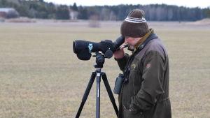 Markku Harmanen står med sin tubkikare vid en grå, vårig åker.