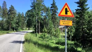 En asfalterad väg med skog på båda sidorna. Till höger syns ett trafikmärke, en triangel som varnar för en liten korsning och jordtransnporter.