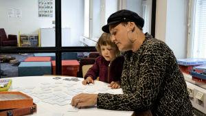 Maria Udd med sin treåriga dotter Wilma Udd spelar memory i spelrummet i biblioteket. I bakgrunden syns lekrummet.