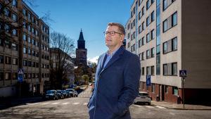 En man i en blå kappa med Åbo domkyrka i bakgrunden