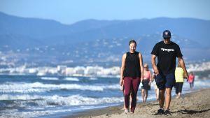 Oskar Osala går på en strand med sin fästmö.