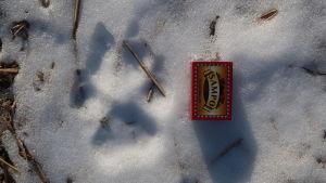 Ett tassavtryck av varg i snö och intill ligger en tändsticksask