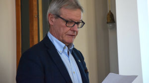 En medelålders man i glasögon tittar på ett papper. I bakgrunden syns en stor skärm.