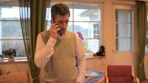 En man talar i telefon. Han finns i ett äldreboende (läkare, men civilt klädd)