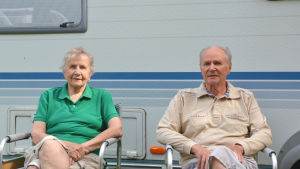 En äldre kvinna och en äldre man sitter framför en husvagn.