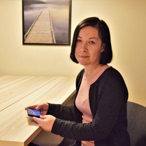 Pia Köpsi, en dam med rosa skjorta och svart tröja, sitter vid ett skrivbord.