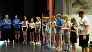 Flickor och en man står i en halvcirkel och sjunger