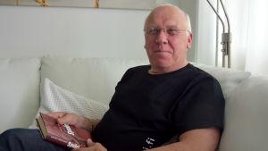 Harri Savunen sitter i en vit lädersoffa och håller en bok i händerna.