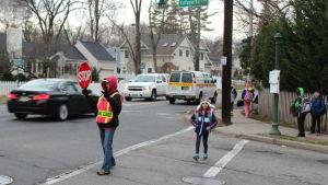 Jennifer Duteil stoppar trafiken medan ett barn går över gatan i Chatham, New Jersey.