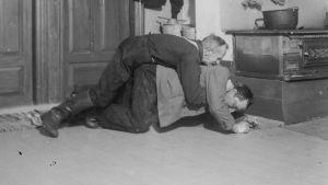 """Två män leker """"ryggbördan"""", där den ena ligger på golvet med den andra på sin rygg, Den undre ska försöka stiga upp, den andra ska hindra den första att göra det."""