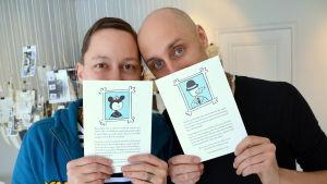 Två konstnärer håller upp bilder på var sitt alter egon