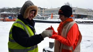 Åsa Bylund bjuder en deltagare på varm saft.