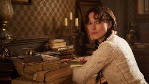 Keira Knightley poserar som Colette vid ett skrivbord.