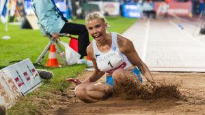 Taika Koilahti landar i sanden och grimaserar.