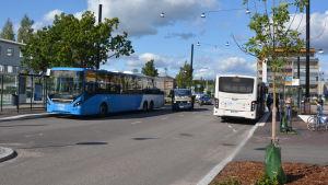 Två bussar på var sin sida vägen vid Nickby bussterminal. Några bilar håller på och kör om en av bussarna.