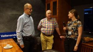 två män och en kvinna som står och diskuterar i ett mötesrum