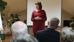 Hanna Guseff står framför en äldre publik med grått hår.