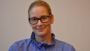 EN kvinna med blåvit skjorta.